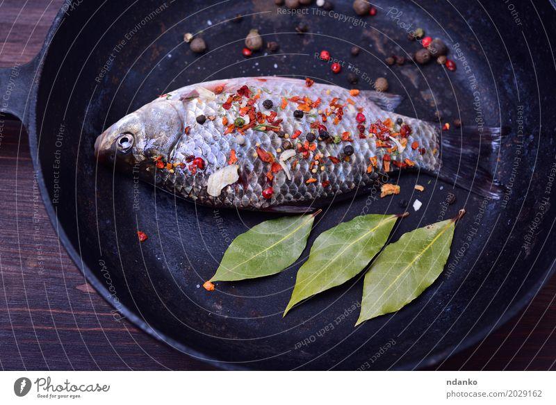 Karpfen mit Gewürzen in einer schwarzen Gusseisenpfanne Natur grün Blatt Essen Holz braun oben frisch Tisch Fisch Kräuter & Gewürze Küche Top roh Zutaten