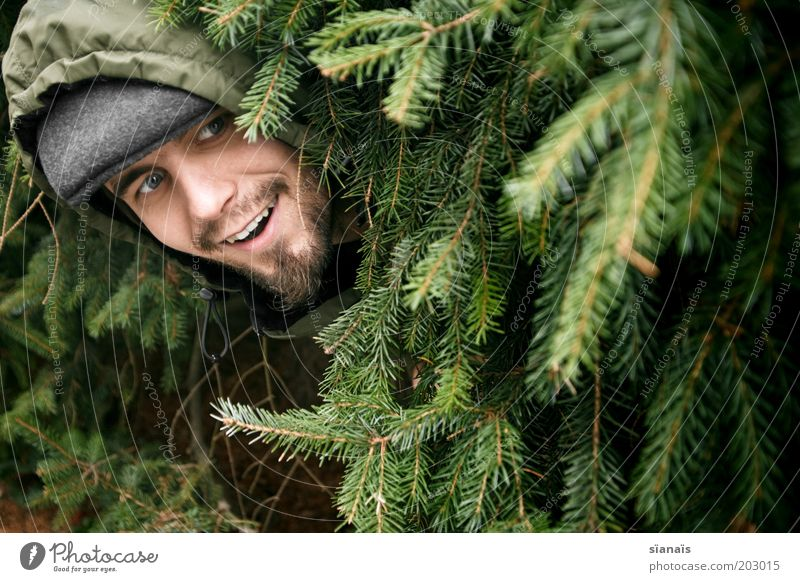 lunschen maskulin Mann Erwachsene Leben Kopf Tanne entdecken Freude verstecken Versteck hervorrufen dumm bescheuert grün Tarnung Tarnfarbe Kapuze lachen Lächeln