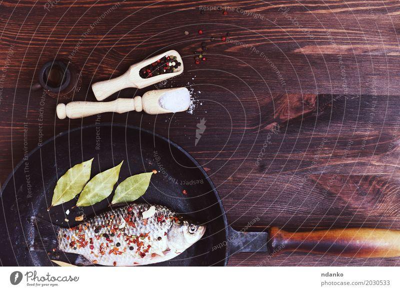 Fischkarpfen mit Gewürzen in einer schwarzen Gusseisenpfanne Lebensmittel Kräuter & Gewürze Pfanne Tisch Küche Natur Blatt Holz Diät Essen frisch natürlich oben