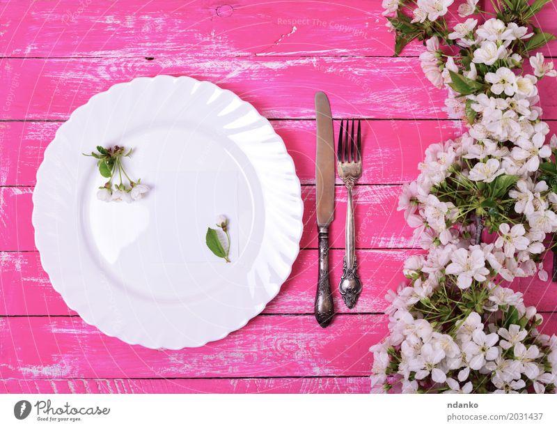 Weißer Teller auf einer rosa Holzoberfläche Mittagessen Abendessen Besteck Messer Gabel Tisch Küche Restaurant Blume Papier Metall Stahl alt oben retro weiß