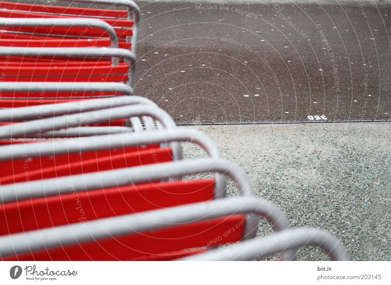abgestellt im Regen Menschenleer grau rot Ordnungsliebe Reinlichkeit Sauberkeit Traurigkeit Einsamkeit Biergarten Stuhl Stuhllehne Klappstuhl Gastronomie