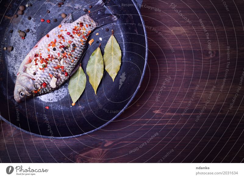 Karpfen mit Gewürzen in einer schwarzen Gusseisenpfanne grün Essen Holz Lebensmittel braun oben Ernährung frisch Tisch Fisch Kräuter & Gewürze Küche Top Diät