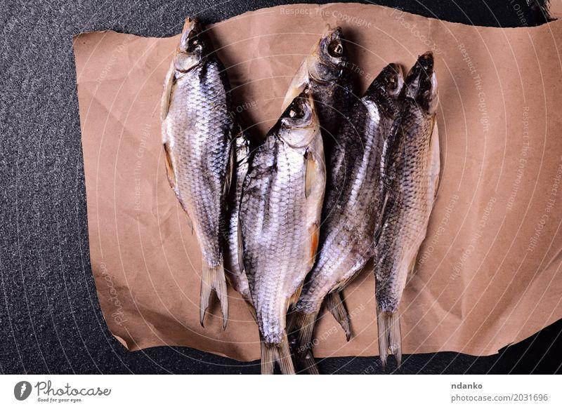 Fischramm ist getrocknet und liegt auf braunem Kraftpapier schwarz Essen Lebensmittel oben Ernährung retro Papier essbar Karpfen Schafsbock Rotauge