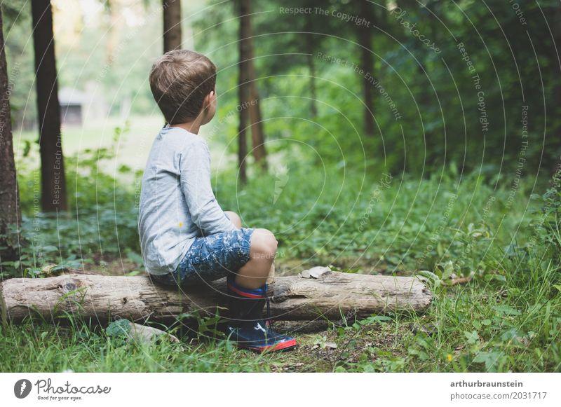 Junge sitzt auf Baumstamm im Wald Mensch Kind Natur Ferien & Urlaub & Reisen Sommer Umwelt Leben Gras Holz Spielen Schule Tourismus Freizeit & Hobby