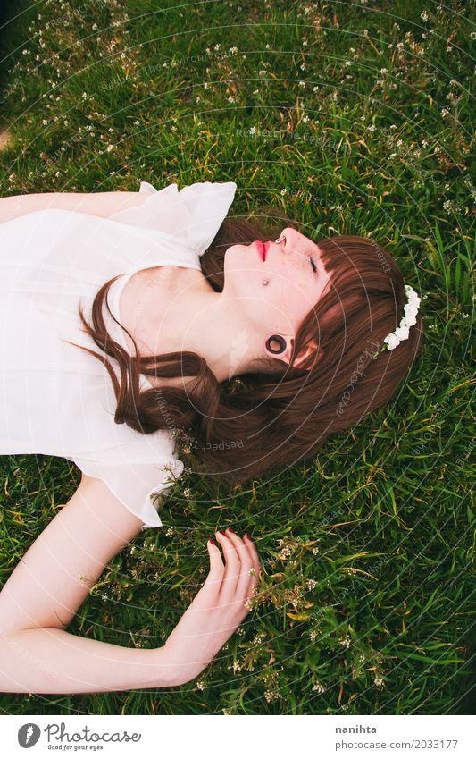 Junge Brunettefrau, die über einem Feld des Grases schläft Lifestyle elegant schön Wellness harmonisch Wohlgefühl Erholung ruhig Meditation Freiheit Mensch