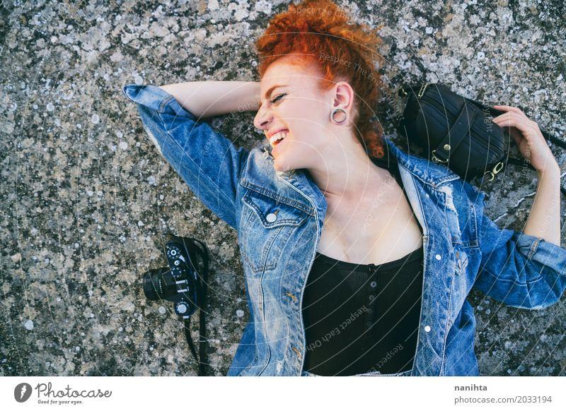 Junge Rothaarigefrau, die auf Boden mit ihrer Tasche und ihrer Kamera liegt Mensch Ferien & Urlaub & Reisen Jugendliche Junge Frau schön 18-30 Jahre Erwachsene