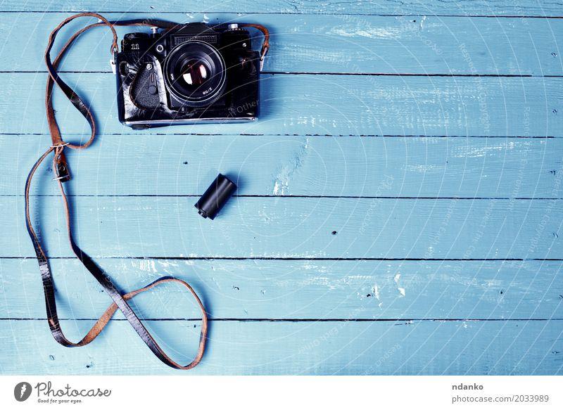 Weinlesekamera in einem ledernen Kasten auf einer blauen Holzoberfläche Fotokamera alt retro braun Fotografie Deckung Leerzeichen Gerät Top schäbig altehrwürdig