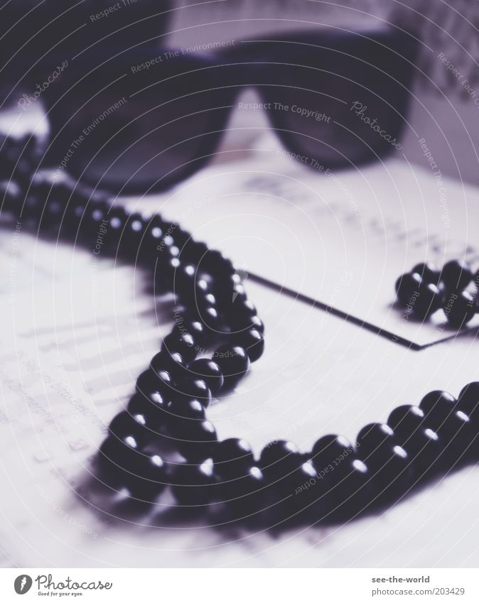 black pearls Halskette Sonnenbrille violett schwarz weiß rund liegen Perle Farbfoto Gedeckte Farben Innenaufnahme Nahaufnahme Reichtum Lifestyle Perlenkette
