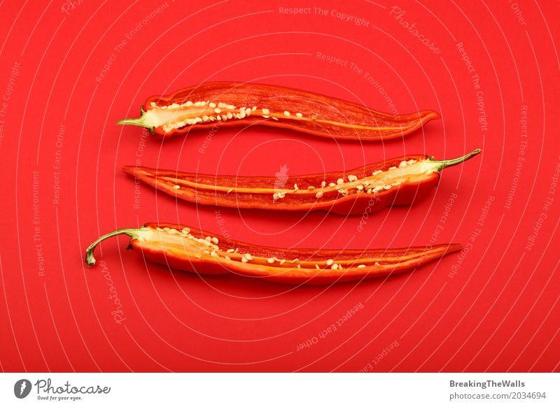 Drei halbierte frische scharfe Paprikapfeffer über Rot Lebensmittel Gemüse Kräuter & Gewürze Ernährung Kunst Papier Aggression heiß rot Farbe Idee Hälfte