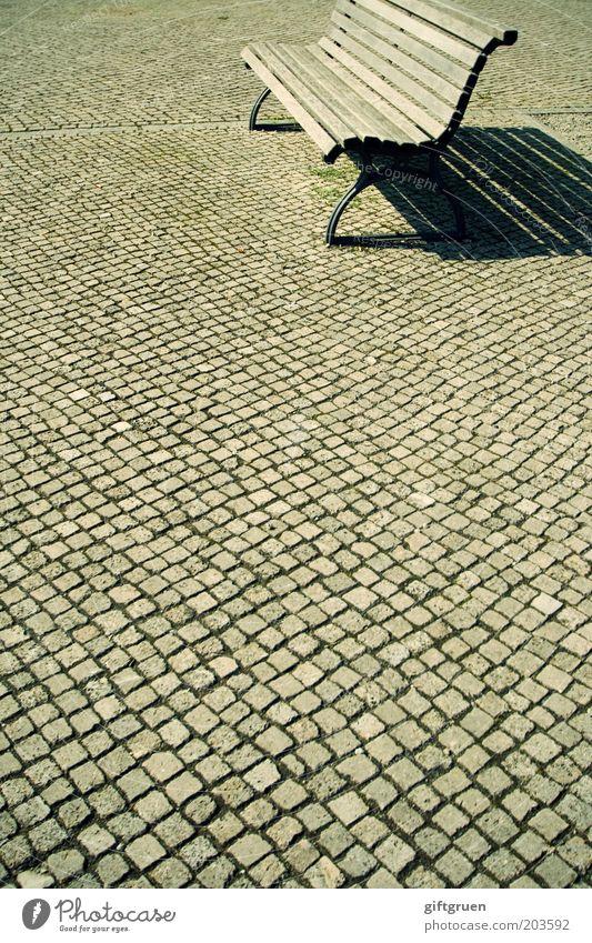 sonnenbank Menschenleer Platz ruhig Langeweile Ferne Bank Parkbank Pause Schatten Sonnenbank Pflastersteine Kopfsteinpflaster Holzbank Einsamkeit