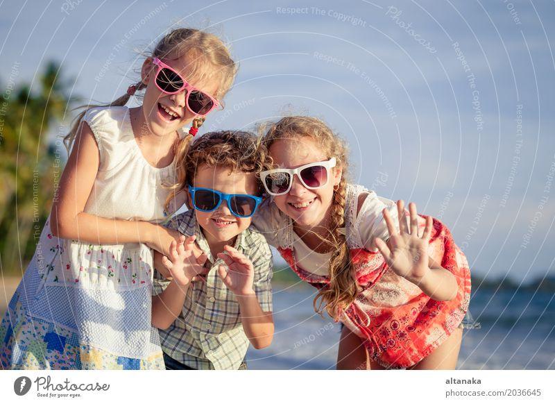 Drei glückliche Kinder, die auf dem Strand zur Tageszeit stehen. Lifestyle Freude Glück schön Erholung Freizeit & Hobby Spielen Ferien & Urlaub & Reisen