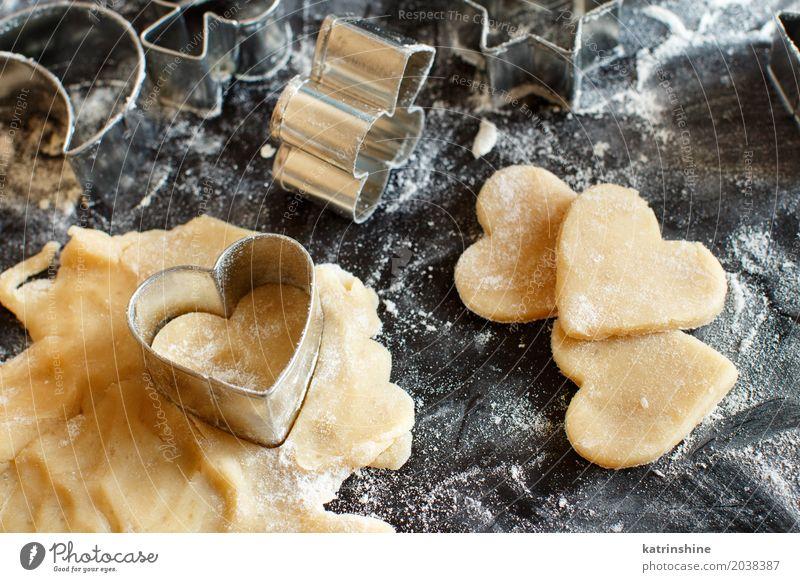 Schließen Sie oben von den Plätzchenschneidern in einem Teig auf einer dunklen Tabelle Teigwaren Backwaren Dessert Küche Herz machen backen Bäckerei Biskuit