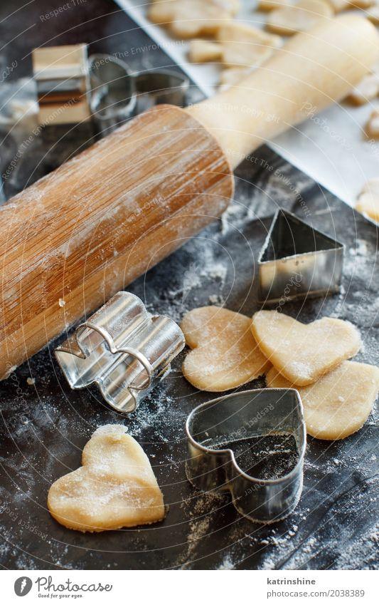 Schließen Sie oben von den Plätzchenschneidern und Nudelholz auf einer dunklen Tabelle Teigwaren Backwaren Dessert Küche Herz machen backen Bäckerei Biskuit