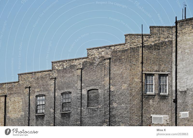 around King´s Cross alt Haus Fenster Wand Gebäude Mauer trist Fabrik aufwärts London Blauer Himmel England Großbritannien Stufendach