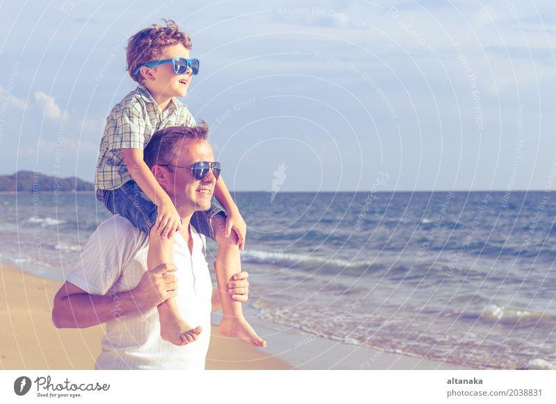 Vater und Sohn, die auf dem Strand zur Tageszeit spielen. Kind Natur Ferien & Urlaub & Reisen Mann Sommer Sonne Hand Meer Erholung Freude Erwachsene Leben
