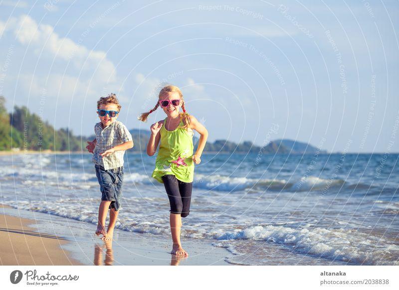 Glückliche Kinder, die auf dem Strand zur Tageszeit spielen. Mensch Natur Ferien & Urlaub & Reisen Sommer Sonne Hand Meer Erholung Freude Lifestyle Gefühle