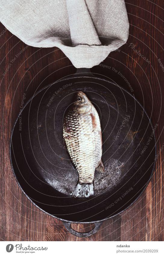 Karpfen der frischen Fische in einer schwarzen Bratpfanne Essen natürlich Holz braun oben Tisch Küche Fleisch Top rustikal roh Zutaten Pfanne