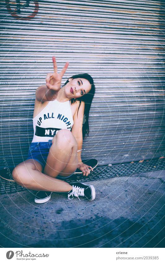 Junge glückliche Frau, die auf dem Skateboard macht Friedenshandzeichen sitzt Lifestyle Freude Freizeit & Hobby Freiheit Mensch feminin Junge Frau Jugendliche