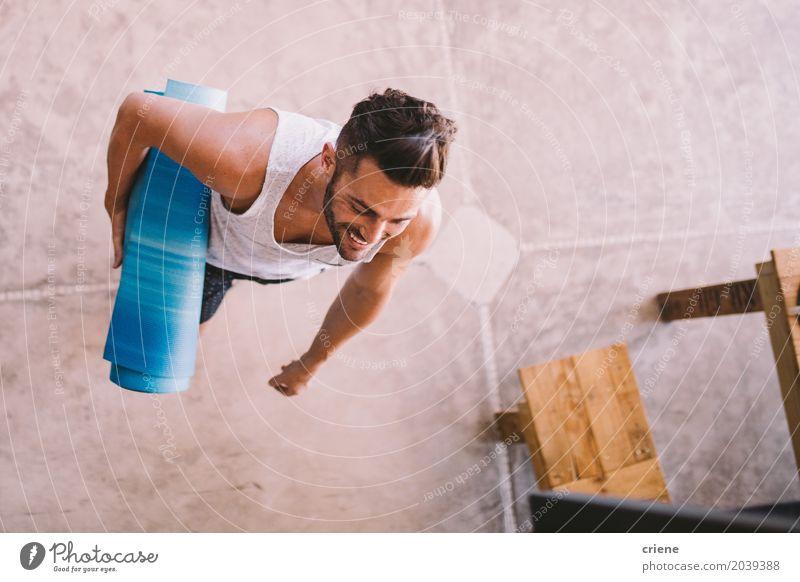 Junger männlicher Erwachsener, der Yogamatte im Wohnzimmer hält Mensch Jugendliche Mann Junger Mann 18-30 Jahre Lifestyle Sport Glück Gesundheitswesen maskulin