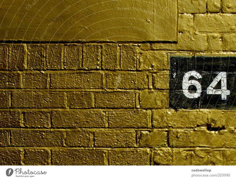 When I'm... Bauwerk Mauer Wand Backstein Ziffern & Zahlen gold schwarz weiß Reichtum 64 Edelstahl Hausnummer Jubiläum Jahrgang veredeln Farbfoto Außenaufnahme