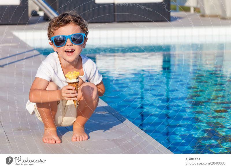 Glücklicher kleiner Junge mit der Eiscreme, die nahe einem Swimmingpool sitzt Mensch Kind Natur Ferien & Urlaub & Reisen Mann Sommer schön Sonne Erholung Freude