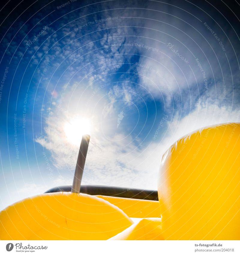 yellow fellow II Vergnügungspark Himmel Wolken Sonne Sonnenlicht Wetter Schönes Wetter Hüpfburg Hüpfschloss groß rund weich blau gelb schwarz weiß aufgeblasen