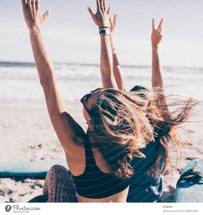 Zwei junge Frau, die mit den Händen oben am Strand zujubelt Lifestyle Freude Freizeit & Hobby Ferien & Urlaub & Reisen Tourismus Abenteuer Freiheit Sommer