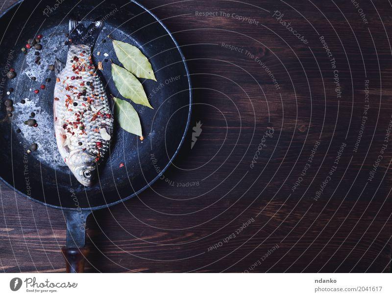 Fisch in Gewürzen auf einer schwarzen Gusseisenpfanne natürlich Holz braun oben Ernährung frisch Tisch Kräuter & Gewürze Küche lecker Top roh Zutaten Pfanne