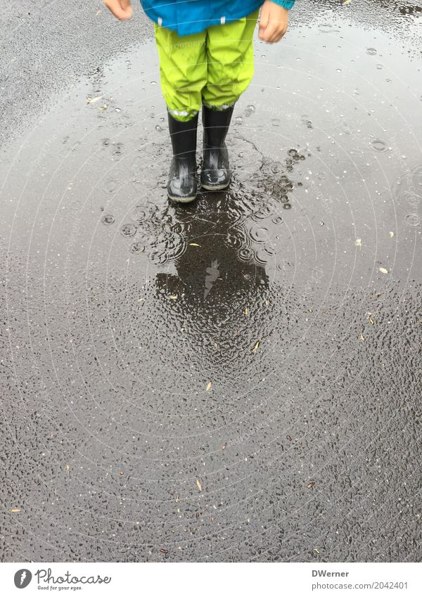 Regenwetter Lifestyle Spielen Abenteuer Tanzen Kindererziehung Junge 1 Mensch Umwelt Natur schlechtes Wetter Straße Schutzbekleidung Stiefel Bewegung springen