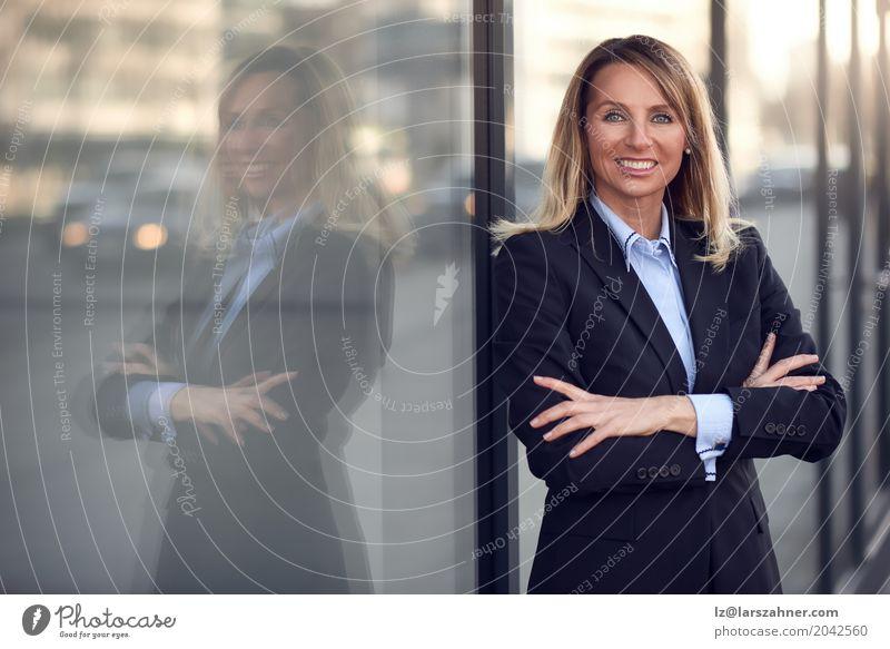 Überzeugter weiblicher Manager, der auf Fenster sich lehnt Glück Business Frau Erwachsene 1 Mensch 30-45 Jahre Anzug blond Lächeln stehen modern blau