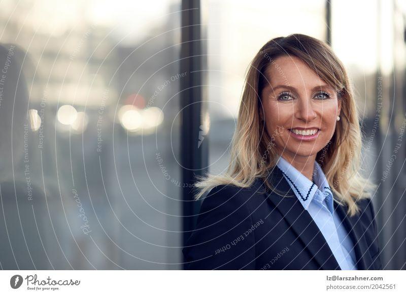 Überzeugter weiblicher Manager, der auf Fenster sich lehnt Glück Gesicht Business Frau Erwachsene 1 Mensch 30-45 Jahre Anzug blond Lächeln stehen modern blau