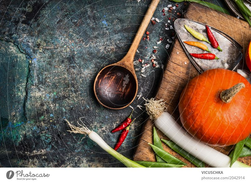 Kürbis auf Küchentisch mit Zutaten und Kochlöffel Lebensmittel Gemüse Kräuter & Gewürze Ernährung Festessen Bioprodukte Vegetarische Ernährung Diät Geschirr