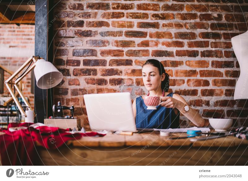 Junge Geschäftsfrau, die an Laptop arbeitet und Kaffee trinkt trinken Lifestyle Freizeit & Hobby Häusliches Leben Schreibtisch Arbeit & Erwerbstätigkeit Büro
