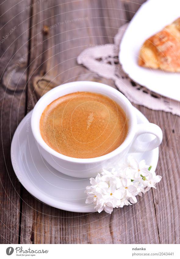 Schwarzer Kaffee in einer weißen Tasse Croissant Dessert Frühstück Espresso Becher Tisch Restaurant Blume Blumenstrauß Holz Essen frisch heiß oben retro braun