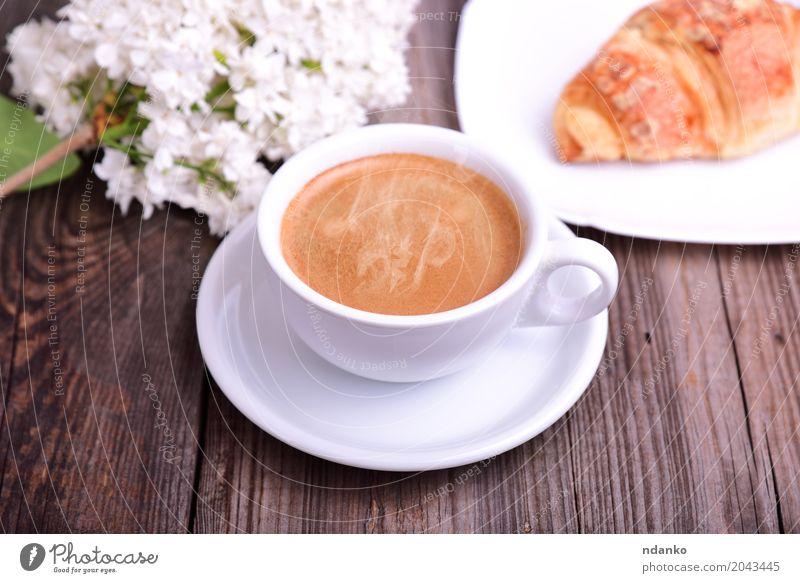 Schale heißer schwarzer Kaffee mit Hörnchen Croissant Frühstück Espresso Tisch Restaurant Blume Blumenstrauß Holz frisch lecker oben retro braun weiß Café