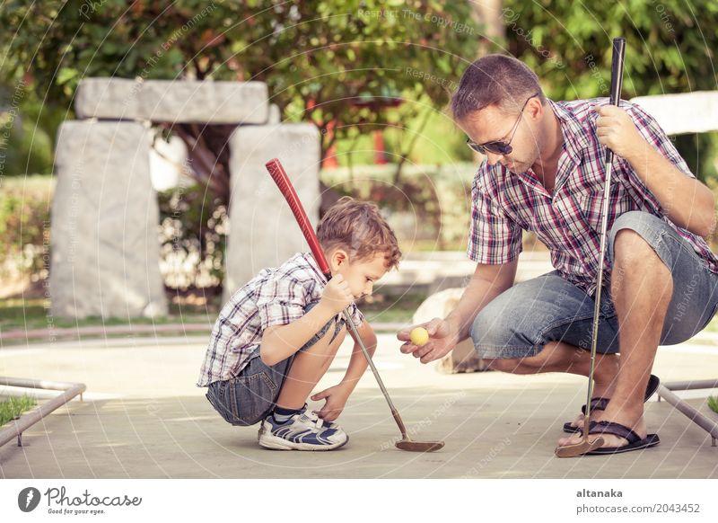 Netter junger Mann, der seinen Sohn unterrichtet, Minigolf zu spielen Mensch Kind Natur Ferien & Urlaub & Reisen Sommer Sonne Erholung Freude Erwachsene