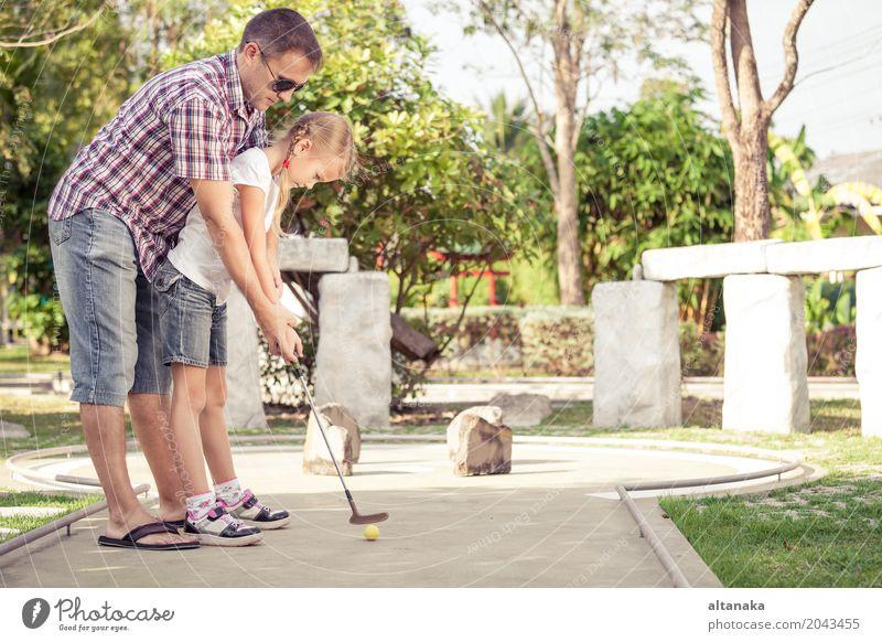 Netter junger Mann, der seine Tochter unterrichtet, Minigolf zu spielen Mensch Kind Natur Ferien & Urlaub & Reisen Sommer Sonne Erholung Freude Erwachsene