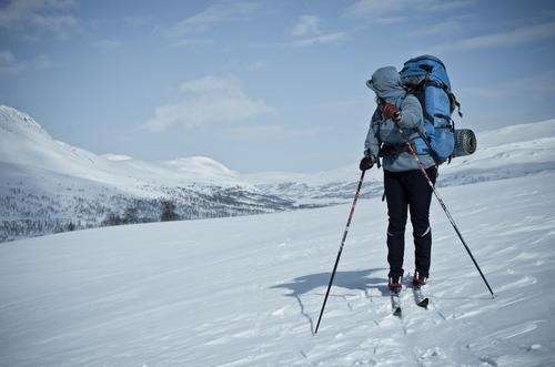 Skiläuferin mit Rucksack in Schneelandschaft, rückwärtsblickend Mensch Natur Ferien & Urlaub & Reisen Jugendliche Junge Frau Landschaft Einsamkeit ruhig Ferne
