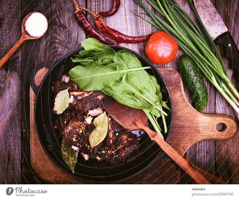 Gebratene Schweinerippchen in Gewürzen auf einer schwarzen Pfanne Fleisch Gemüse Kräuter & Gewürze Löffel Tisch Holz Essen frisch retro grün rot Schweinefleisch