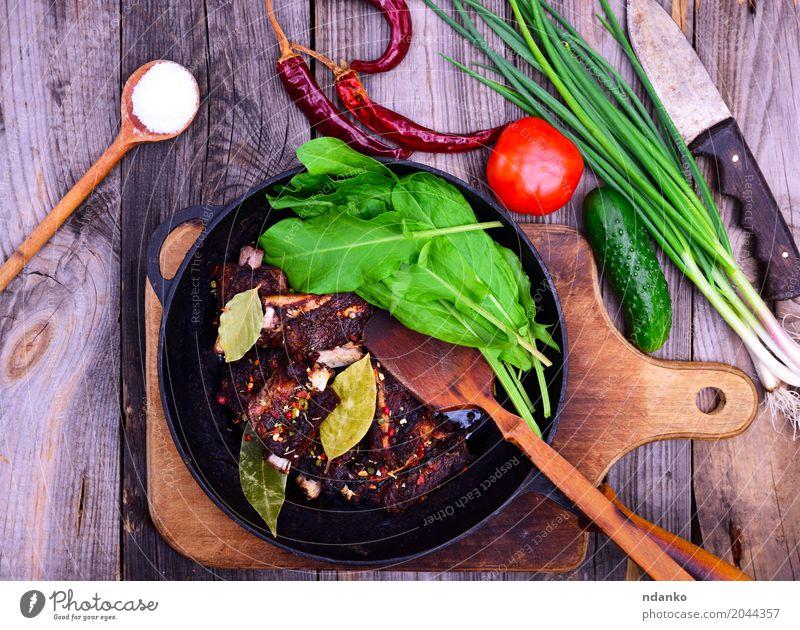 Gebratene Schweinerippchen in Gewürzen Fleisch Gemüse Kräuter & Gewürze Pfanne Holz frisch lecker grün rot schwarz Schweinefleisch Rippen Gitter Tomate Zwiebel