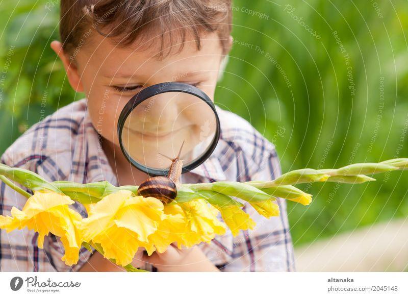 Glücklicher kleiner Junge, der im Park mit Schnecke zur Tageszeit spielt. Mensch Kind Natur Mann Sommer Erholung Freude Erwachsene Lifestyle
