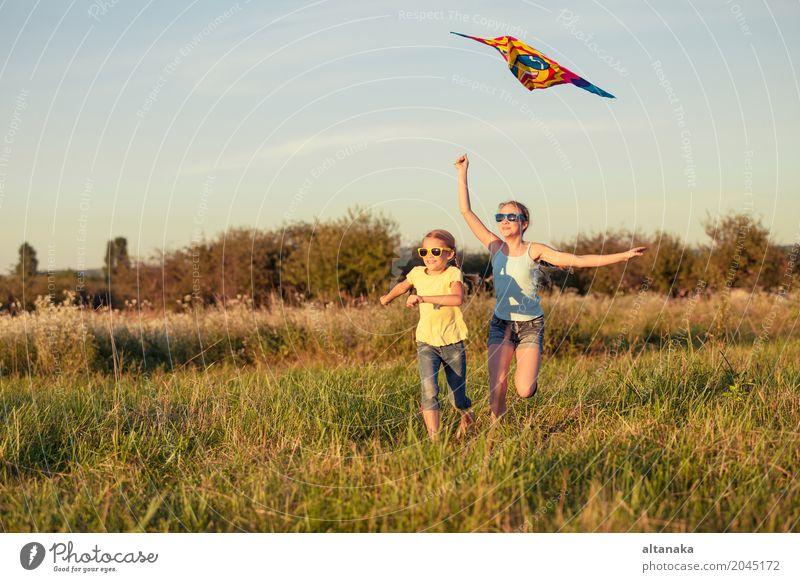 Glückliche Kinder, die auf dem Feld zur Tageszeit spielen. Mensch Himmel Natur Ferien & Urlaub & Reisen Sommer schön Hand Freude Lifestyle Wiese Gras