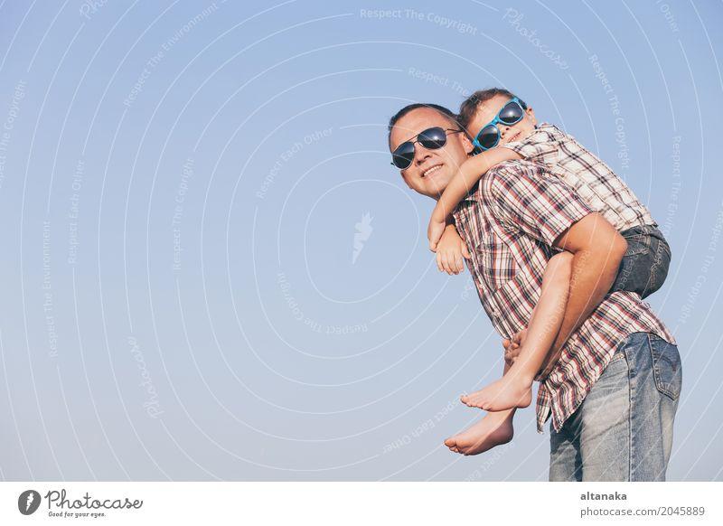 Vati und Sohn in der Sonnenbrille, die im Park zur Tageszeit spielt. Kind Ferien & Urlaub & Reisen Mann Sommer Erholung Freude Erwachsene Leben Lifestyle Liebe