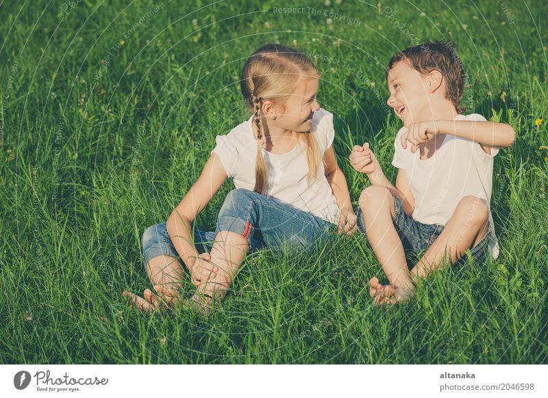 Zwei glückliche Kinder, die nahe einem Baum auf dem Gras spielen Mensch Natur Ferien & Urlaub & Reisen Sommer schön grün Freude Gesicht Lifestyle Liebe Wiese