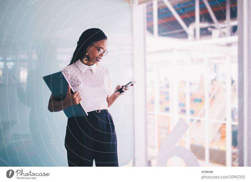 Junge afroamerikanische Geschäftsfrau nutzt Smartphone im Büro Lifestyle lesen Erfolg Arbeit & Erwerbstätigkeit Kapitalwirtschaft Business Karriere PDA Notebook