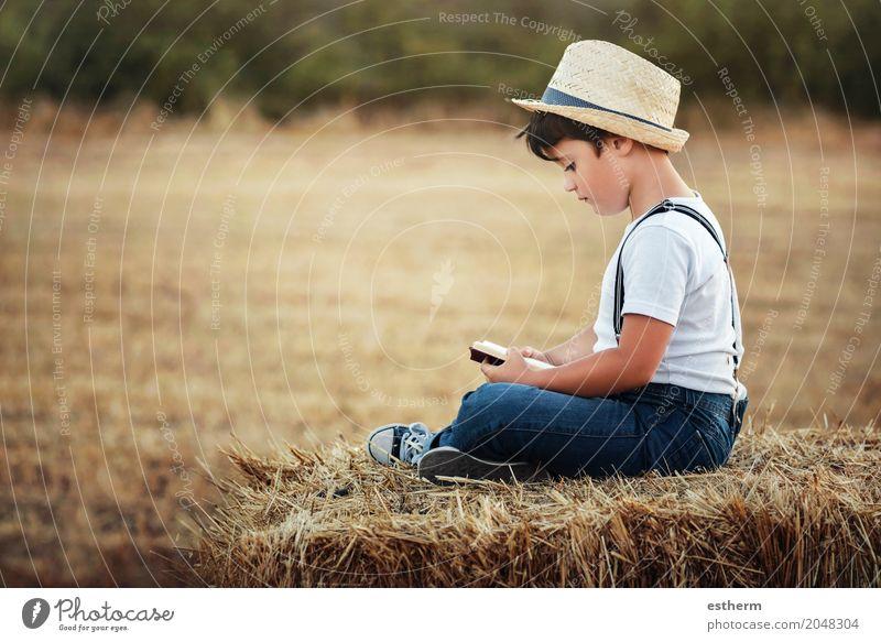 Junge, der ein Buch auf dem Gebiet liest Mensch Kind Natur Ferien & Urlaub & Reisen Landschaft Einsamkeit Freude Lifestyle Wiese Glück Freizeit & Hobby Feld