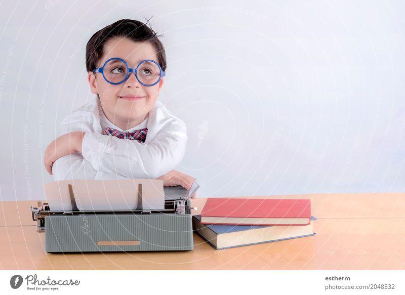 Lächelnder Junge mit Schreibmaschine Mensch Kind ruhig Lifestyle Gefühle Schule Kindheit genießen Abenteuer lernen Coolness Neugier schreiben Bildung