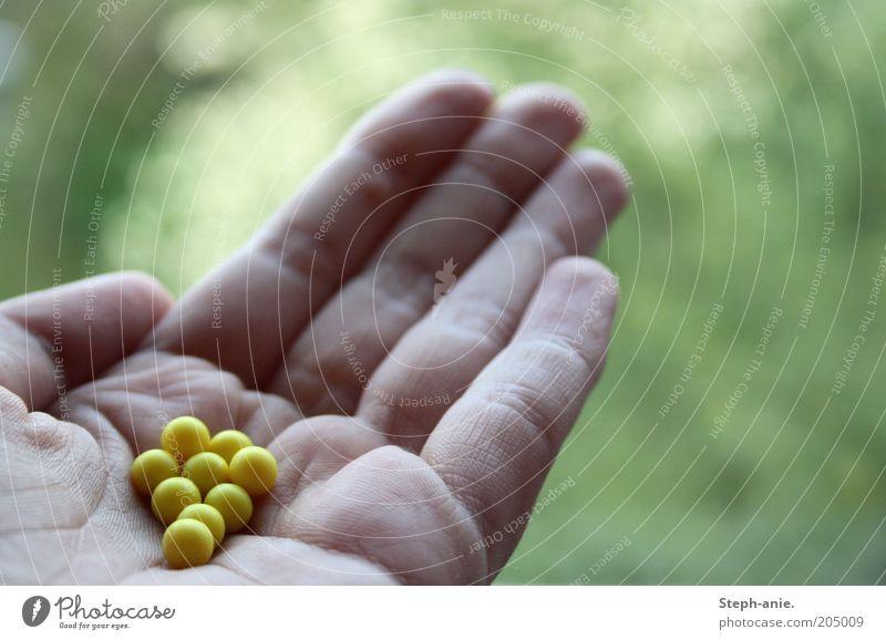 Blumenperlen Kunststoff klein gelb grün Unschärfe Geschenk Kugel Perle zeigen Bonbon Finger Liebesperlen Alternativmedizin Hand geben schenken Textfreiraum oben