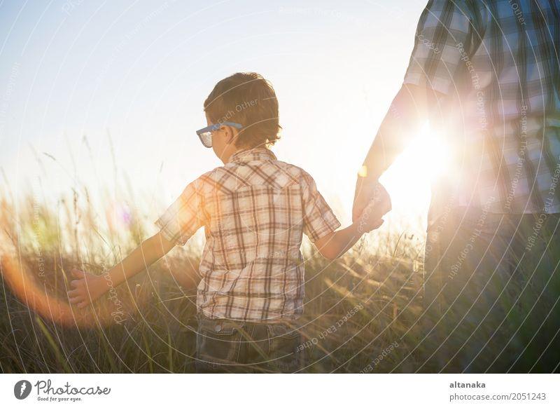 Vater und Sohn, die auf dem Feld zur Tageszeit spielen. Kind Natur Ferien & Urlaub & Reisen Mann Sommer Sonne Hand Erholung Freude Erwachsene Leben Lifestyle