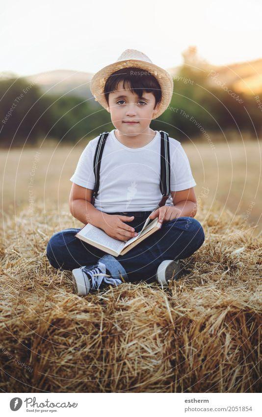 Junge liest ein Buch Mensch Kind Ferien & Urlaub & Reisen Erholung Freude Lifestyle Freiheit Freizeit & Hobby maskulin träumen Kindheit Fröhlichkeit Lächeln